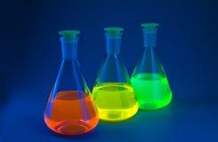 Fluorescência em umas garrafas no azul Foto de Stock Royalty Free