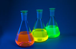 Fluorescence in flasks on blue Royalty Free Stock Photo