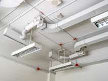 Fluorescence lamp installed on ceiling. Showing tube line and ventilating system Stock Images