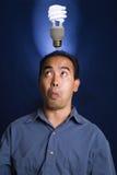 Fluorescent Bulb Idea. Asian / Filipino model with an idea - as shown by a compact fluorescent bulb over head Royalty Free Stock Image