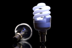 Fluorescent bulb and incandescent bulb. Isolated from black background Royalty Free Stock Photo