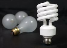 Fluorescent with Incandescent. Energy saver compact fluorescent light bulb with inefficient incandescent bulbs in the background Stock Photo