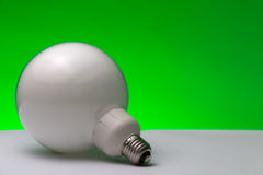 Fluorescent Lamp: Green Energy. Close up of an energy-saving fluorescent lamp with green background for recalling the concept of green energy royalty free stock photography