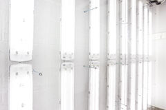 The fluorescent lamps. Hanging on the wall there are various tube lamps stock photo