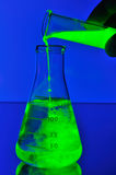 Fluorescent liquid falling in flask Royalty Free Stock Photography