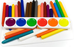 Fluorescent paints and oil  crayons. On white board Royalty Free Stock Images