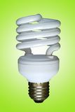 Fluorescent spiral lamp. On green background Royalty Free Stock Photos