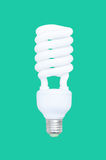 Fluorescent spiral light bulb isolated on green background stock photography