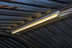 Fluorescent tube in a garage. Fluorescent tube on the ceiling of an old metal garage royalty free stock image
