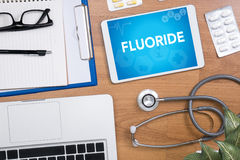 FLUORIDE. Professional doctor use computer and medical equipment all around, desktop top view Royalty Free Stock Photos