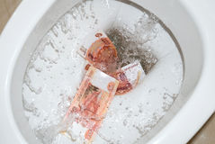 Flush money in the toilet. Flush money in the white toilet Royalty Free Stock Photography