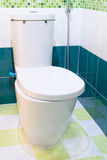 Flush toilet seat with green tile Royalty Free Stock Image
