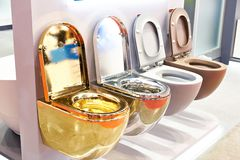 Flush toilet in store. Golden, silver and plastic flush toilet in the store royalty free stock photos