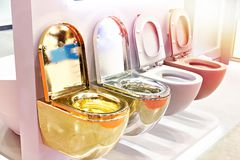 Flush toilet in store. Golden, silver and plastic flush toilet in the store royalty free stock images