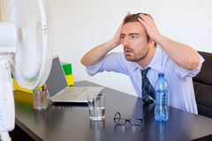Flushed employee feeling. Hot in front of a fan stock photography