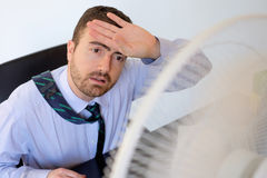 Flushed employee feeling hot. In front of a fan Stock Photo