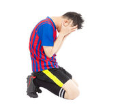 Flushed football player kneeling down. In studio stock photography