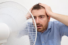 Flushed man feeling hot. In front of a fan stock image