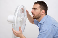Flushed man feeling hot. In front of a fan royalty free stock photos