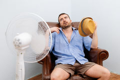 Flushed man feeling hot. In front of a fan stock photography