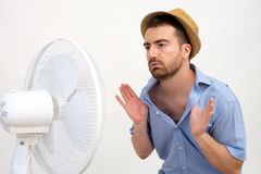 Flushed man feeling hot. In front of a fan royalty free stock images