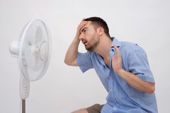 Flushed man feeling hot. In front of a fan royalty free stock image