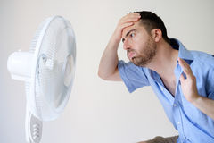 Flushed man feeling hot in front of a fan Royalty Free Stock Photos
