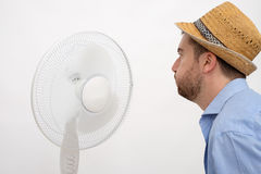 Flushed man feeling hot in front of a fan Royalty Free Stock Image