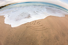 2016 Flushing away with sea foam. Sea foam flushing out digits 2016 from sand on sandy beach. New year is coming and old one go home royalty free stock photography