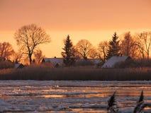 Fluss Atmata, Häuser und schneebedeckte Bäume in den Sonnenuntergangfarben, Litauen stockfoto