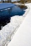 Fluss in den Winter- und Eisstücken und in den landwirtschaftlichen Häusern. Lizenzfreie Stockfotos