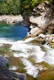 Fluss, der über Felsen in Sommerwald fließt Lizenzfreies Stockbild