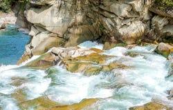 Fluss, der über Felsen in Sommerwald fließt Lizenzfreie Stockbilder