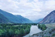Fluss, der in der Dämmerung unter den Bergen fließt Stockfotografie