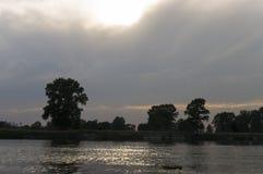 Fluss, der herüber mit Reflexionen im Wasser läuft Abendsonnenuntergang mit Rosa- und Veilchenfarben im Himmel Schattenbilder Stockfotografie