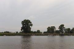 Fluss, der herüber mit Reflexionen im Wasser läuft Abendsonnenuntergang mit Rosa- und Veilchenfarben im Himmel Schattenbilder Stockfoto