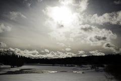 Fluss, der längs schneebedeckte Banken leitet Stockbild