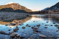 Fluss, der in Richtung zu den Sonnenuntergang-Lit-Bergen führt Stockbilder