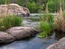 Fluss, der unter den Felsen fließt Stockfotos