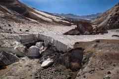 Fluss, der unter die starke eisige Schicht des Gletschers innerhalb des Mutnovsky-Vulkankraters überschreitet stockfoto