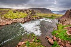 Fluss, der zu einen Wasserfall, Island führt Lizenzfreie Stockbilder