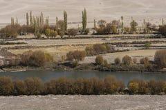 Fluss fließen Ackerland mit Bäumen im Herbst durch Stockfotos