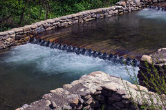 Fluss fließt die hölzernen Klotz durch, die durch Steingrundlage eingezäunt werden Stockbilder