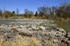 Fluss fließt die Stromschnellen durch Stockfotos