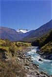 Fluss fließt hinunter das Tal durch Neuseeland von einem Schnee mit einer Kappe bedeckten Berg Stockbild