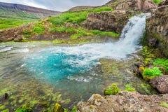 Fluss fließt von einem Wasserfall, Island Stockfotos