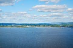 Fluss gegen den blauen Himmel mit Wolken und Wald stockbild