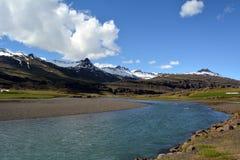 Fluss gegen den Hintergrund von Schnee-mit einer Kappe bedeckten Spitzen der Berge des Basalts in den Ostfjorden von Island Stockbild