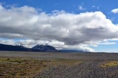 Fluss gegen den Hintergrund von Schnee-mit einer Kappe bedeckten Spitzen der Berge des Basalts in den Ostfjorden von Island Lizenzfreie Stockbilder