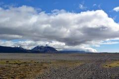 Fluss gegen den Hintergrund von Schnee-mit einer Kappe bedeckten Spitzen der Berge des Basalts in den Ostfjorden von Island Lizenzfreie Stockfotos